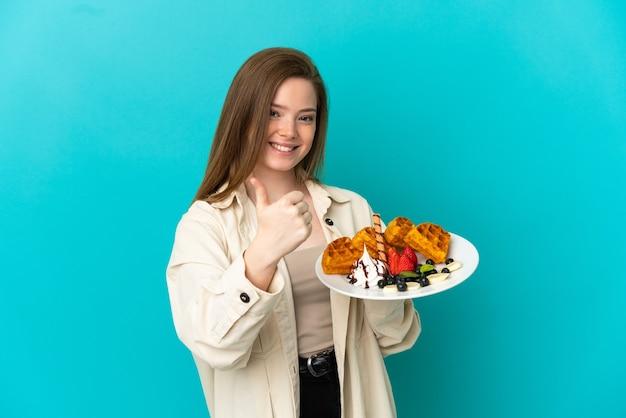 Menina adolescente segurando waffles sobre um fundo azul isolado e fazendo um gesto de polegar para cima