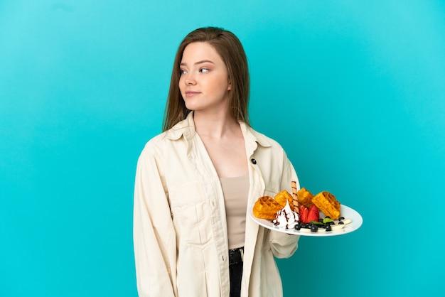 Menina adolescente segurando waffles sobre um fundo azul isolado, olhando para o lado