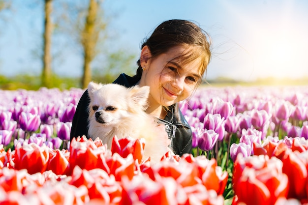 Menina adolescente sentada em campos de tulipas na região de amsterdã, holanda. paisagem mágica da holanda com campo de tulipas