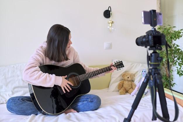 Menina adolescente sentada em casa na cama com um violão, garota aprendendo a tocar violão online. tecnologia, redes sociais, arte, hobby, conceito de adolescentes