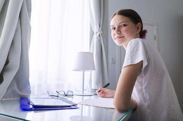 Menina adolescente sentada estudando na mesa em casa perto da janela, estudante escrevendo no caderno