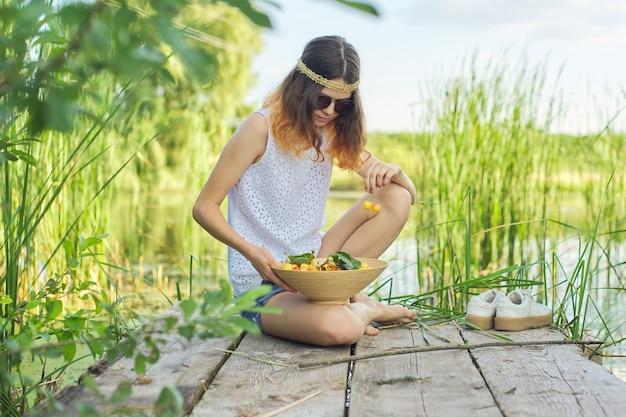 Menina adolescente sentada no cais de madeira com cerejas amarelas. mulher jovem e bonita comendo frutas naturais e apreciando o pitoresco pôr do sol no lago. beleza, comida saudável, natureza, espaço de cópia
