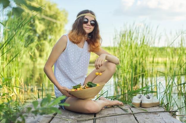 Menina adolescente sentada no cais de madeira com cerejas amarelas