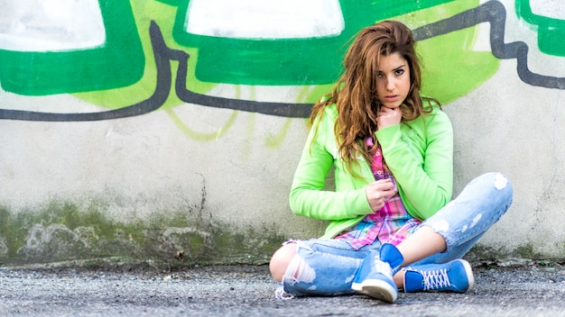 Menina adolescente sentado no chão ao longo de uma parede de graffiti