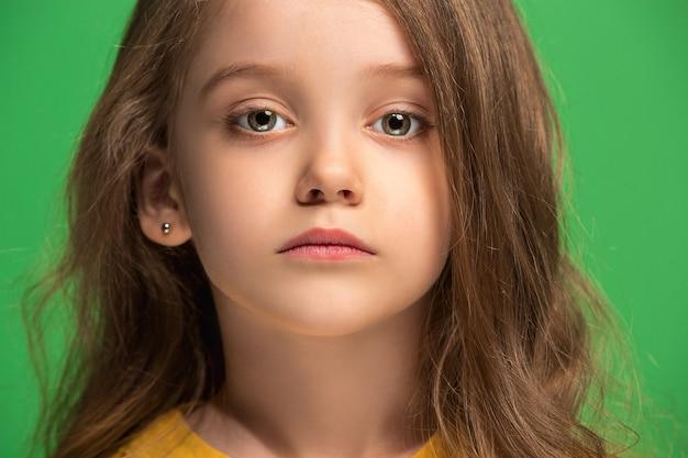 Menina adolescente séria, triste, duvidosa e pensativa em pé no estúdio verde