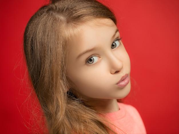 Menina adolescente séria, triste, duvidosa e pensativa em pé no estúdio vermelho