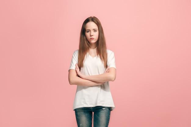 Menina adolescente séria, triste, duvidosa e pensativa em pé no estúdio