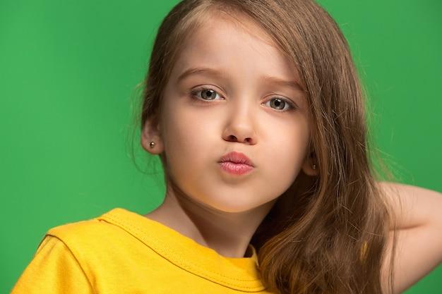 Menina adolescente séria, triste, duvidosa e pensativa em um estúdio verde
