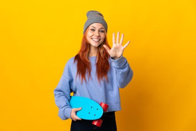 Menina adolescente skatista russa isolada em fundo amarelo contando cinco com os dedos