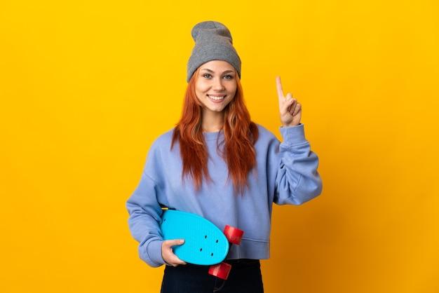 Menina adolescente skatista russa isolada em um fundo amarelo apontando para uma ótima ideia