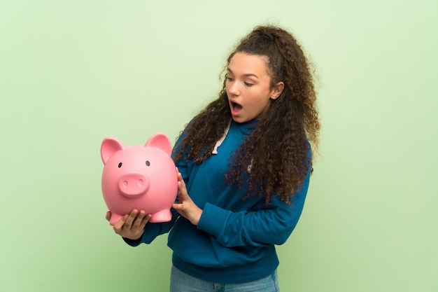 Menina adolescente sobre a parede verde surpreendida enquanto segura um piggybank