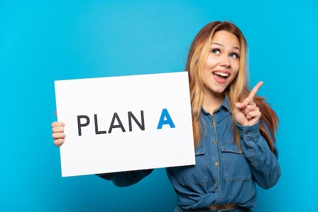 Menina adolescente sobre fundo azul isolado segurando um cartaz com a mensagem plano a e pensando