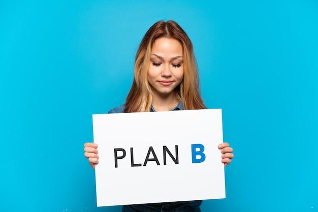 Menina adolescente sobre fundo azul isolado segurando um cartaz com a mensagem plano b