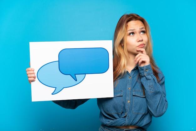 Menina adolescente sobre fundo azul isolado segurando um cartaz com o ícone de balão de fala e pensando