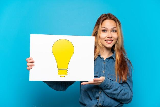 Menina adolescente sobre fundo azul isolado segurando um cartaz com o ícone de lâmpada e apontando-o