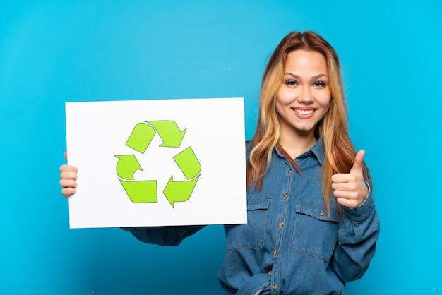 Menina adolescente sobre fundo azul isolado segurando um cartaz com o ícone de reciclagem com o polegar para cima