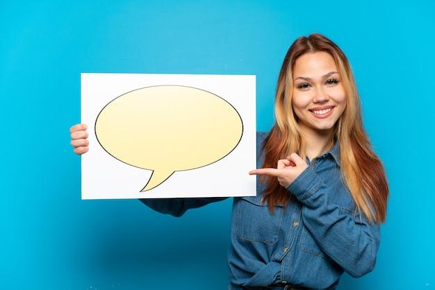Menina adolescente sobre fundo azul isolado segurando um cartaz com o ícone de um balão de fala e apontando-o