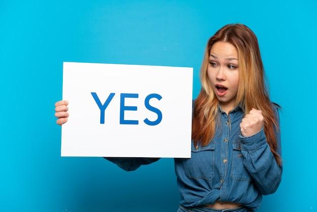 Menina adolescente sobre fundo azul isolado segurando um cartaz com o texto sim e comemorando uma vitória