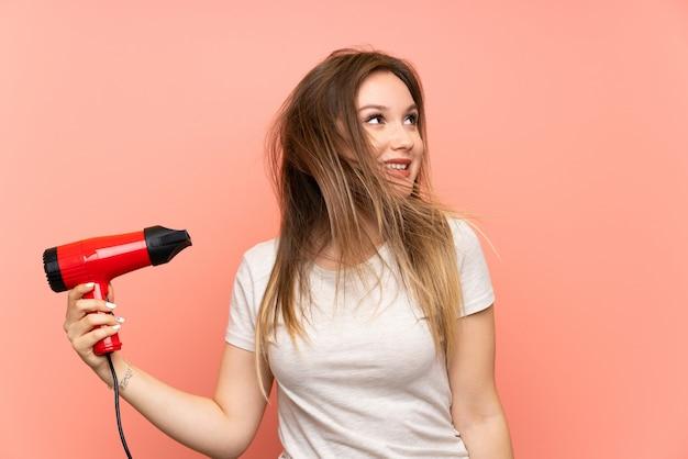 Menina adolescente sobre fundo rosa com secador de cabelo