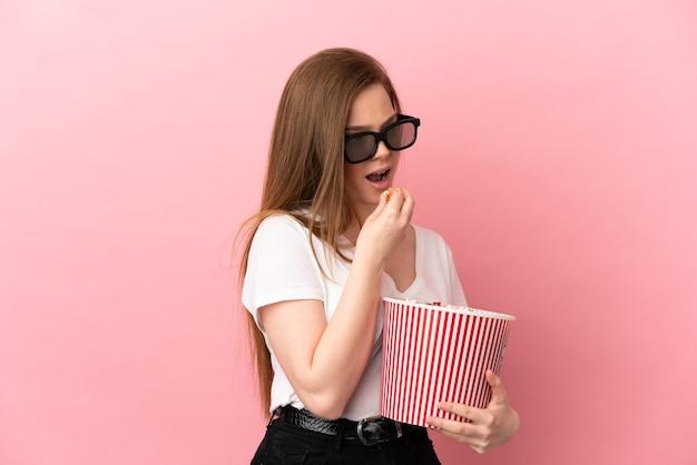 Menina adolescente sobre fundo rosa isolado com óculos 3d e segurando um grande balde de pipocas enquanto olha para o lado