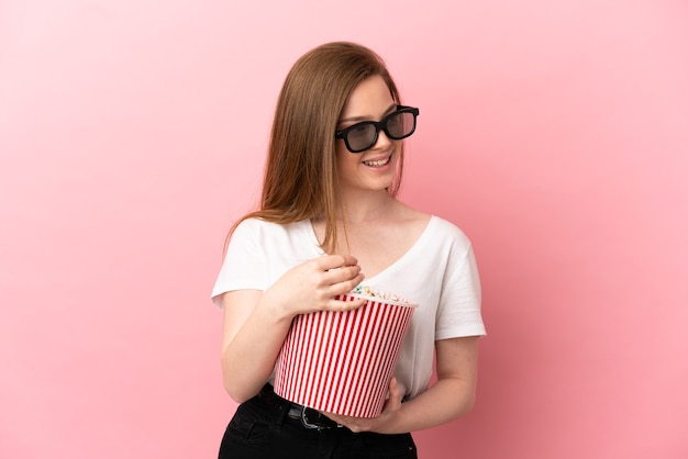 Menina adolescente sobre fundo rosa isolado com óculos 3d e segurando um grande balde de pipocas