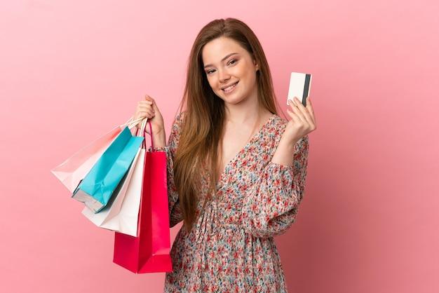 Menina adolescente sobre fundo rosa isolado segurando sacolas de compras e um cartão de crédito
