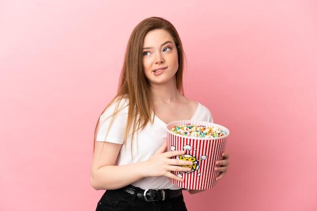 Menina adolescente sobre fundo rosa isolado segurando um grande balde de pipocas