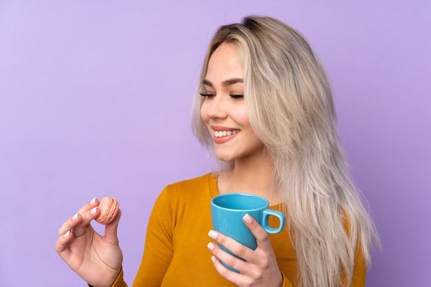 Menina adolescente sobre fundo roxo isolado segurando macarons franceses coloridos e um copo de leite