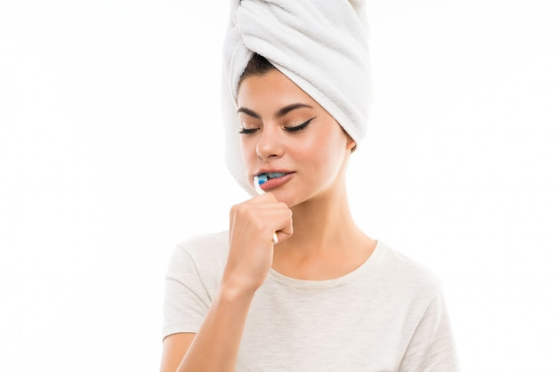 Menina adolescente sobre parede branca isolada, escovando os dentes