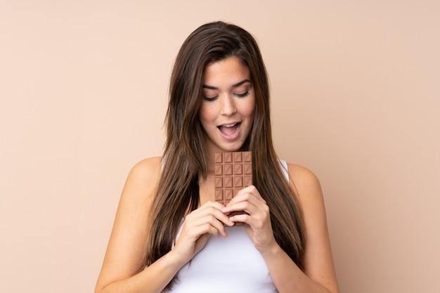 Menina adolescente sobre parede isolada, comendo uma tablete de chocolate