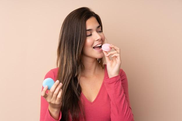 Menina adolescente sobre parede isolada segurando macarons franceses coloridos e comê-lo