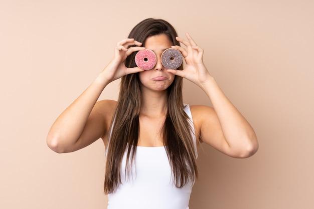 Menina adolescente sobre parede isolada segurando rosquinhas nos olhos com expressão triste