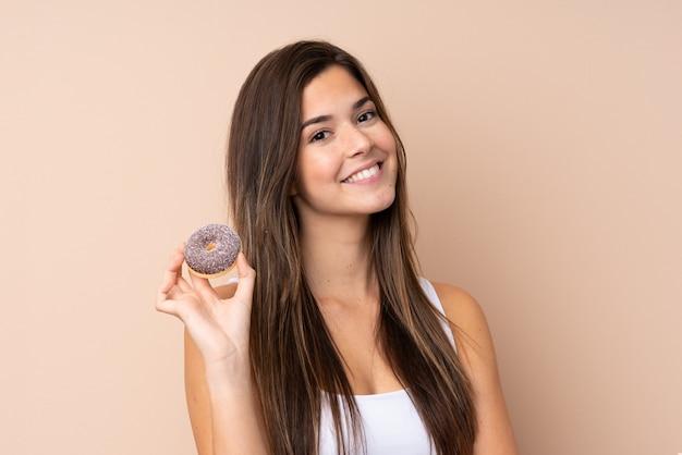 Menina adolescente sobre parede isolada, segurando uma rosquinha e feliz