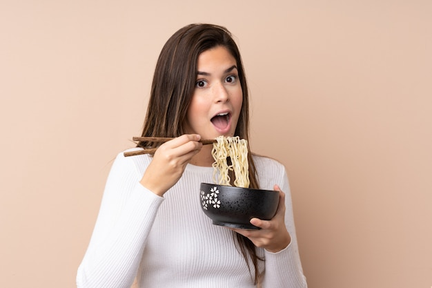 Menina adolescente sobre parede isolada, segurando uma tigela de macarrão com pauzinhos e comê-lo