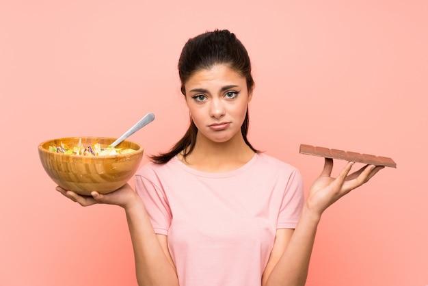 Menina adolescente sobre parede rosa isolada com salada e chocolat e ter dúvidas