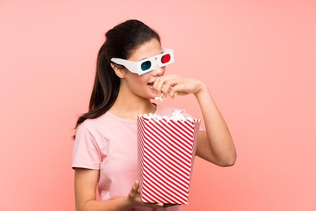 Menina adolescente sobre parede rosa isolada comendo pipocas com óculos 3d