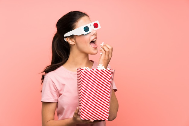 Menina adolescente sobre parede rosa isolada, comendo pipocas com óculos 3d