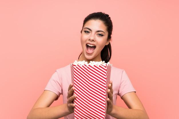 Menina adolescente sobre parede rosa isolada comendo pipocas fazendo gesto surpresa