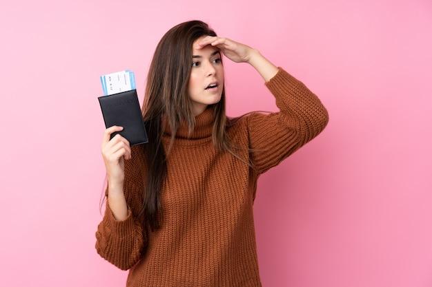 Menina adolescente sobre parede rosa isolada em férias com bilhetes de passaporte e avião enquanto procura algo à distância