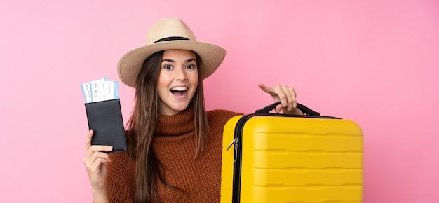 Menina adolescente sobre parede rosa isolada em férias com mala e passaporte e surpresa
