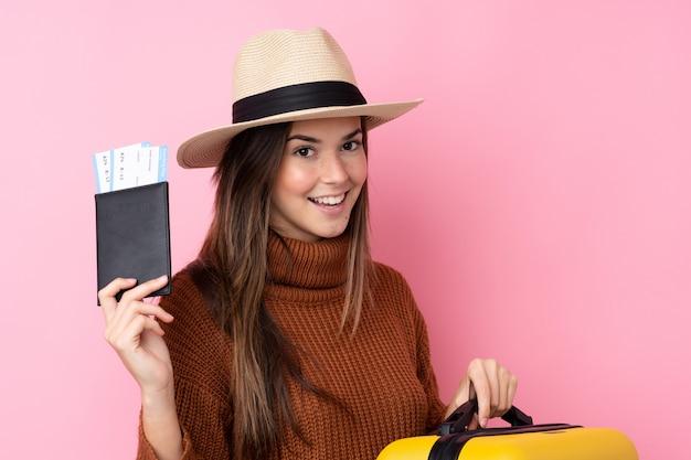 Menina adolescente sobre parede rosa isolada em férias com mala e passaporte
