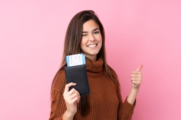 Menina adolescente sobre parede rosa isolada em férias segurando um passaporte e avião com o polegar