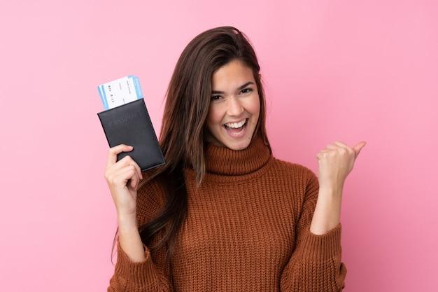 Menina adolescente sobre parede rosa isolada feliz em férias com bilhetes de avião e passaporte