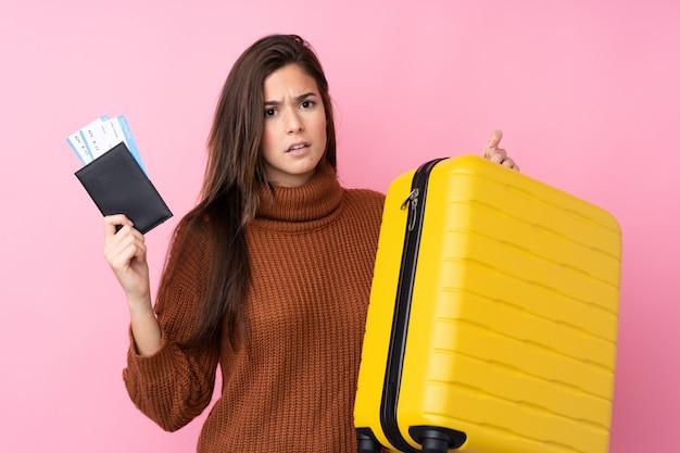 Menina adolescente sobre parede rosa isolada infeliz em férias com mala e passaporte
