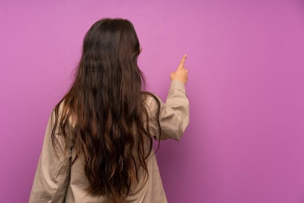 Menina adolescente sobre parede roxa, apontando para trás com o dedo indicador