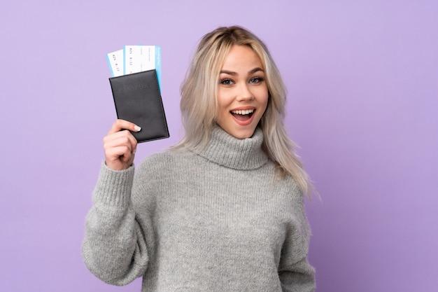Menina adolescente sobre parede roxa isolada feliz em férias com bilhetes de avião e passaporte