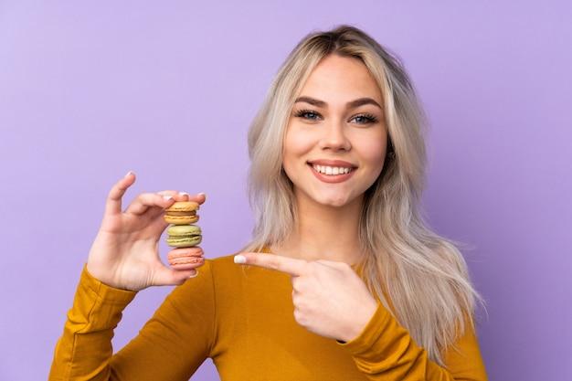 Menina adolescente sobre parede roxa segurando macarons franceses coloridos e apontando-o