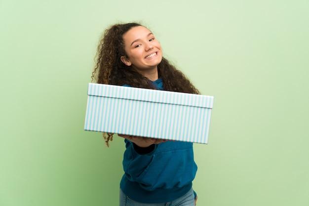 Menina adolescente sobre parede verde segurando um presente nas mãos