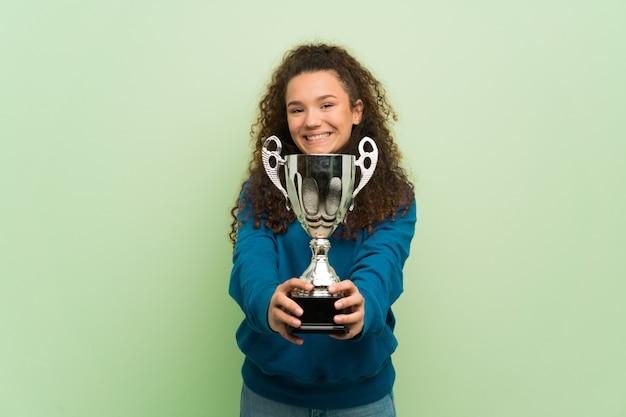 Menina adolescente sobre parede verde segurando um troféu