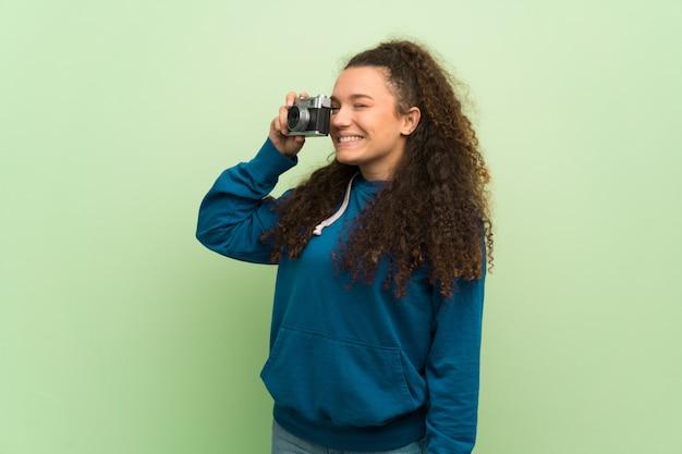 Menina adolescente sobre parede verde segurando uma câmera